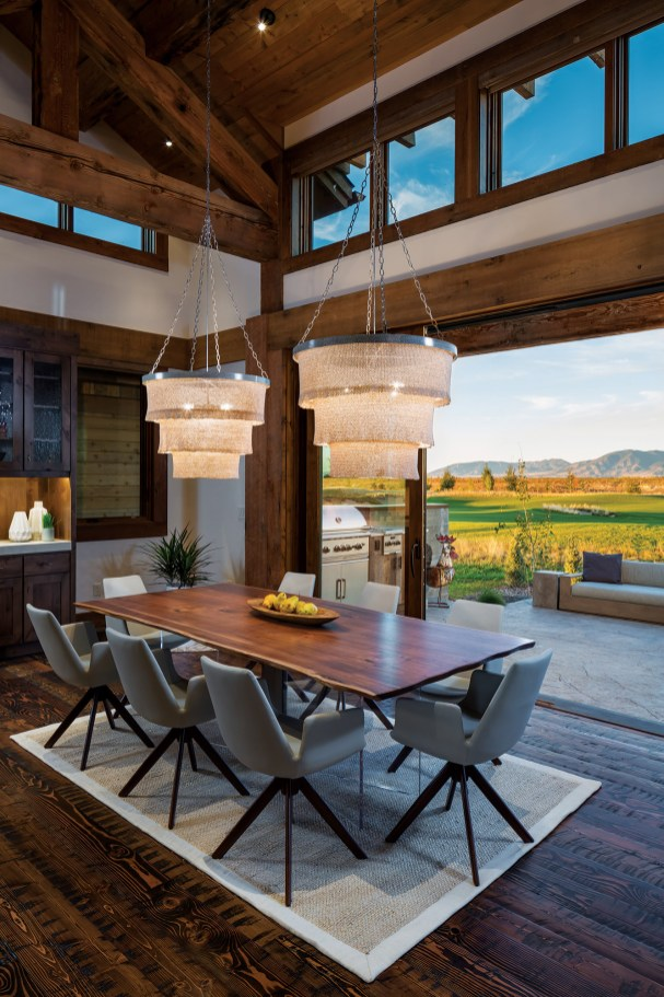 The dining area in the great room opens to the outside through large, lift-and-slide doors.