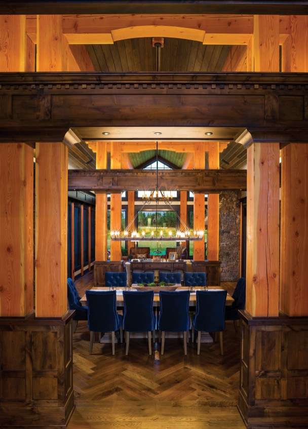 In the dining room, refined details such as herringbone flooring, cornices, dentil moulding and recessed ceilings soften rustic elements of stately exposed timber columns and stone walls.