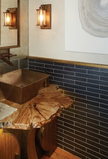 A copper sink and fixtures pair unexpectedly with slab wood and art-deco elements.