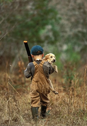 A young hunter and lab puppy head afield ... just like Dad.