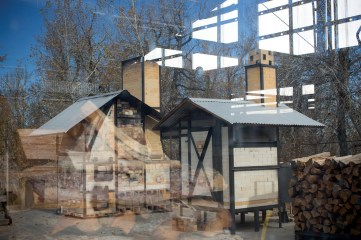 Wood kilns are reflected in a studio window.