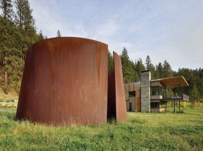 A Richard Serra sculpture stands a distance from the house, its rusted steel echoing that of the home's roof and siding.