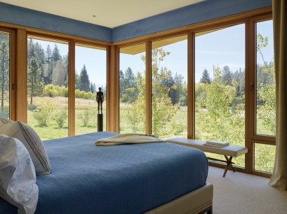 The master bedroom is a serene sanctuary in blue, and a Henry Moore sculpture stands silhouetted before the views of the meadow and aspens.