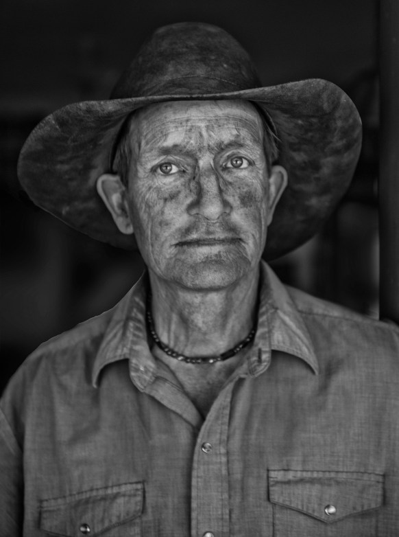"""Photographer Adam Jahiel describes cowboy Ord Buckingham, right, as a historian, horse trainer, musician, philosopher, and veteran of many years of work on the Willow Creek Ranch. """"At the end of a long day moving cattle along the Red Wall, Buckingham was covered with the dust from the red sandstone that surrounds the ranch."""""""