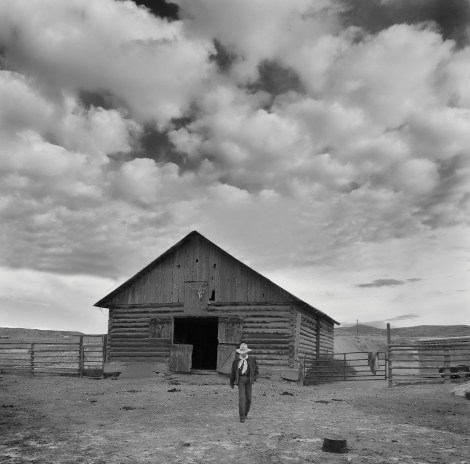 Willow Creek Ranch cowboy Mike Burkich walks from the horse barn as afternoon clouds roll in.