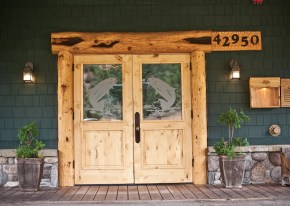 The double doors of the Rainbow Ranch Lodge are etched with two jumping trout.