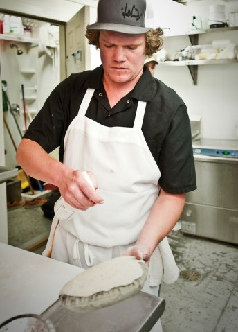 In the kitchen, a sous chef prepares the naan for the tandoor oven.