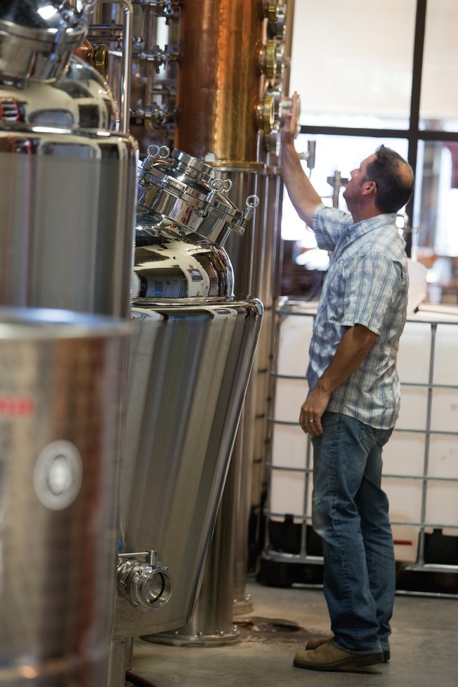 Owner Jim Harris checks a pressure gage on one of his copper columns.