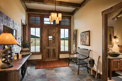 Little touches, like the speakeasy door in the main entry and the outhouse-inspired bathroom to the foyer's right, add a bit of whimsy and humor to the home's elegance.