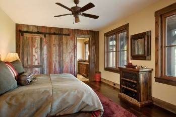 In the guest room, repurposed barn wood and a sliding barn door continue the dwelling's Western theme.