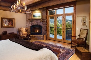 A gas fireplace warms the master bedroom that looks toward Lone Peak.