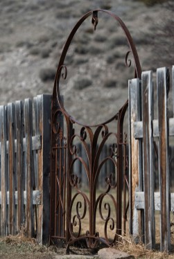Curls and arches by Bar Mill Iron Forge contrast beautifully with the vertical repeats of a weathered fence.