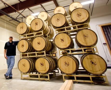 Owner Bryan Schultz stands next to the barrels. The inside of the barrels are charred and act like tea bags, steeping just the right amount of caramelized sugar, oils and tannins into the whiskey.