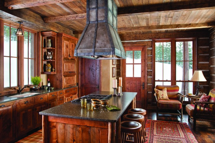 In the kitchen, aged fir/pine cabinetry with a raised panel door design, edges are eased with detailed chiseling and hand sanding. The island integrates log pole corners for additional detail, and the cabinetry is complimented with stone countertops and a custom-built wrought iron hood.