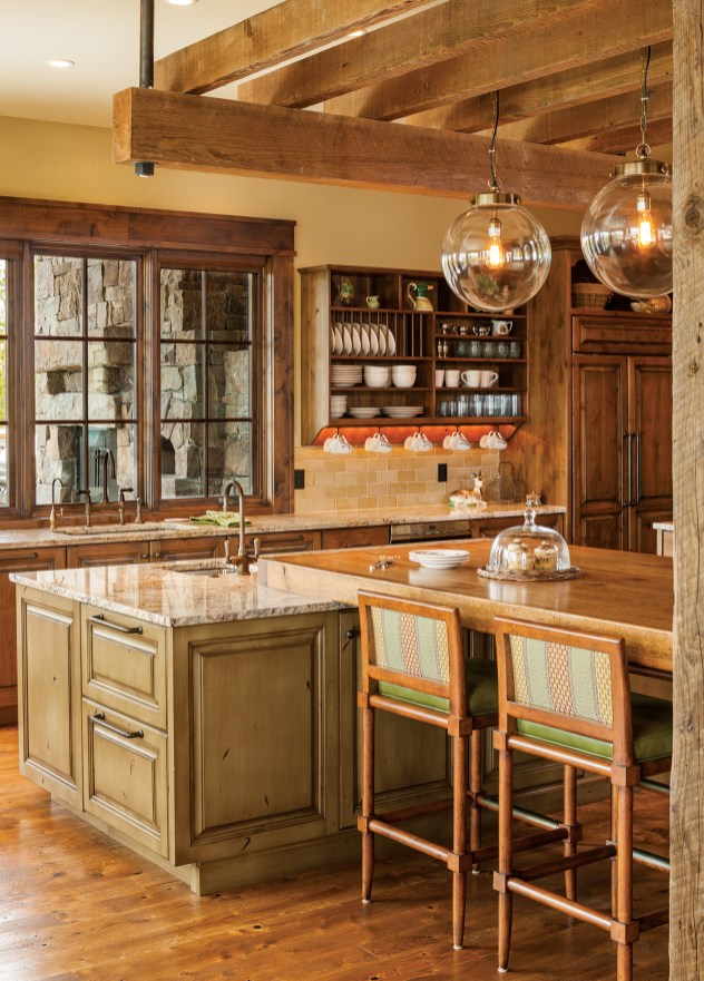 Kitchen lighting varies from the functional, such as the under-thecounter lights and the recessed lighting in the ceiling, to the decorative, like the glass pendants hanging over the island. Photo courtesy Erika & Company