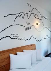 "Designer Jeremy Sandlin created a wall infographic of ""a fictitious [mountain] range composed of the area's tallest peaks."""