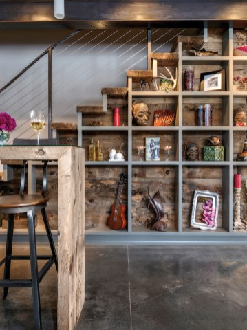 Bookshelves built from recycled timber store treasures under the floating staircase.