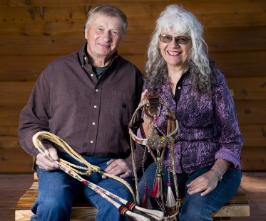 """Ron and Shoni Maulding form a great artistic duo. They have combined the art of Shoni's hitched horsehair with Ron's creative metal, rawhide, and semi-precious stonework. They are holding one of their most unique pieces, called """"Mariposa."""""""