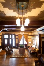 The ceiling of the main lobby is decorated with vintage wallpaper, and all of the wood work, as well as the ceiling light fixtures, are original.