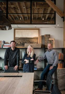 Joe Roodell, far left, Candace Tillotson-Miller, and Matt Miller, stand proudly in the conference room of the new office. be