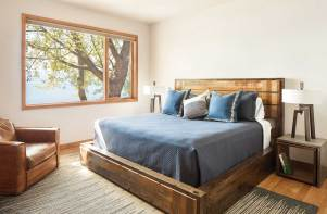 Blue hues and knotted wood furniture in the bedrooms harmonize with its exterior surroundings.