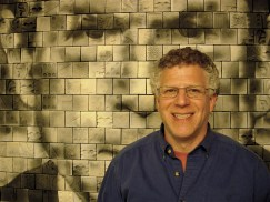 """Artist Richard Notkin in front of his mural """"All Nations Have Their Moment of Foolishness."""""""
