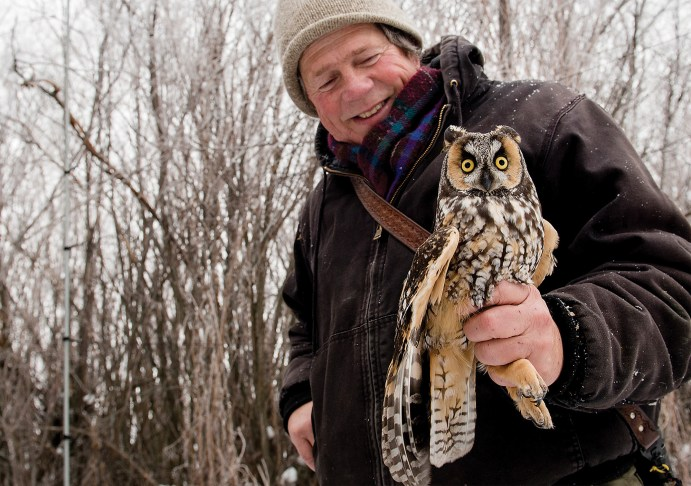 Denver Holt smiles while his crew collects data on three long-eared owls they netted near Missoula, Montana. Holt started studying owls while working on a wildlife degree at the University of Montana.
