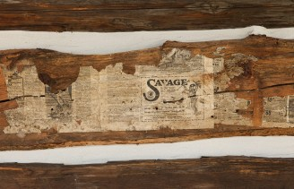 A close-up of an old newspaper ad for a 1910 Savage rifle that was found on one of the reclaimed logs.