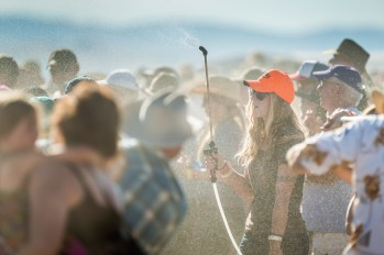 Cool down: Without a stick of shade for miles, a Red Ants Pants volunteer spritzes the crowd with water.