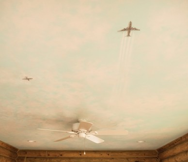 "Using a laborious method known as ""dry brushing,"" Reece painted this ceiling mural with a sky scene. The old-fashioned propeller plane passing the modern airplane symbolizes the project's motif: new and old meeting under one roof."
