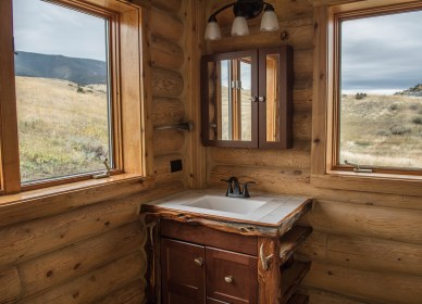 This bathroom, one of two, is well-lit with windows featuring mountain views.