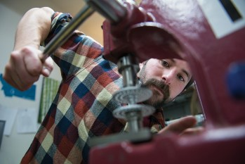 Chris Stroili uses a hand press to insert a part on a S-Handle Classic spool.