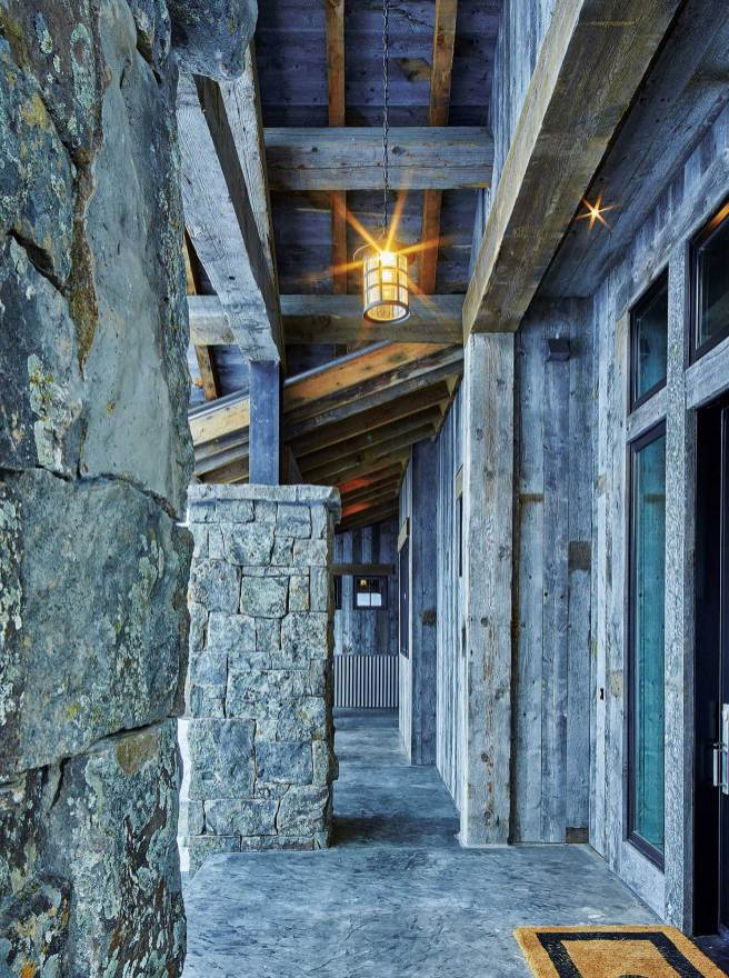 The exterior is a blend of stone, reclaimed lumber, and steel, fitting organically into the natural surroundings.