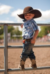 A little cowboy climbs the gate angling for a better view.