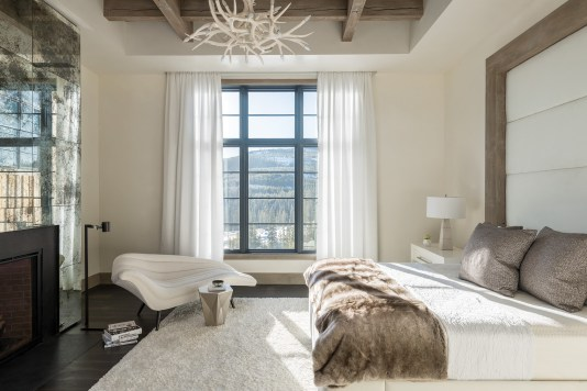 The master bedroom incorporates unique finishes, such as a mirrored wall of glass that conceals a television.