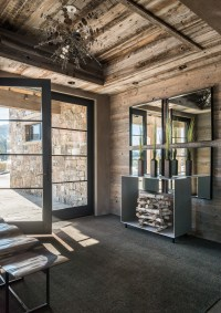 The home's elegant, formal entry leads to a staircase that climbs to the second-floor guest suites and third-floor master suites. On either side of the entry is a discreet caterer's kitchen and a gear room for skis.