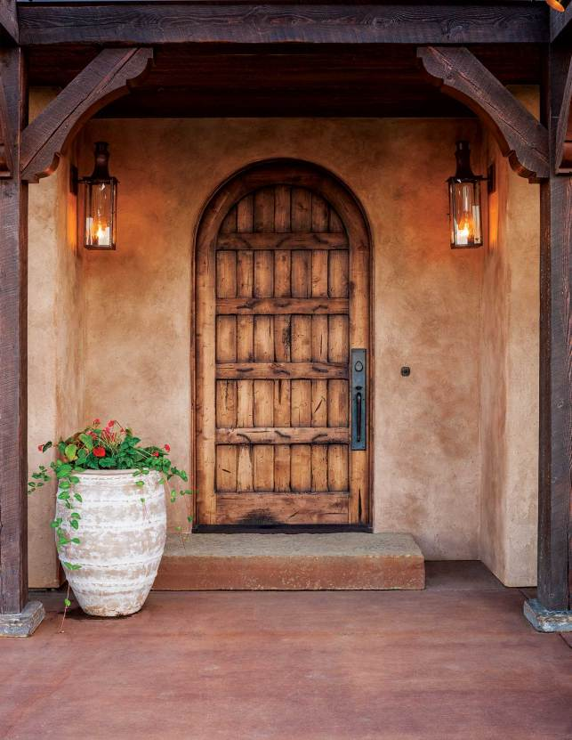 An arched, Tuscan-style door framed with fir beams welcomes visitors.