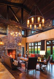 The great room features a floor to eaves fireplace and fir-beamed ceiling.