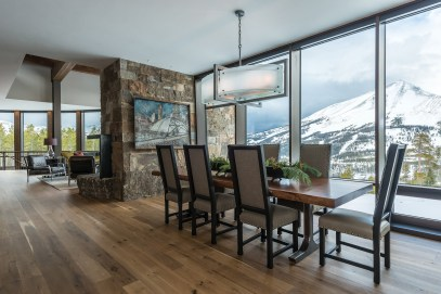 The dining room table, made from a 100-yearold walnut slab, was custom built by Elements Artisan Concrete, and the chandelier is a custom piece from Iron Glass Lighting. The dining room chairs are from Gallatin Valley Furniture.