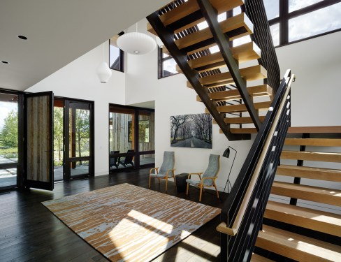 A central staircase with open risers and streamlined design creates a sculptural element in the entryway.