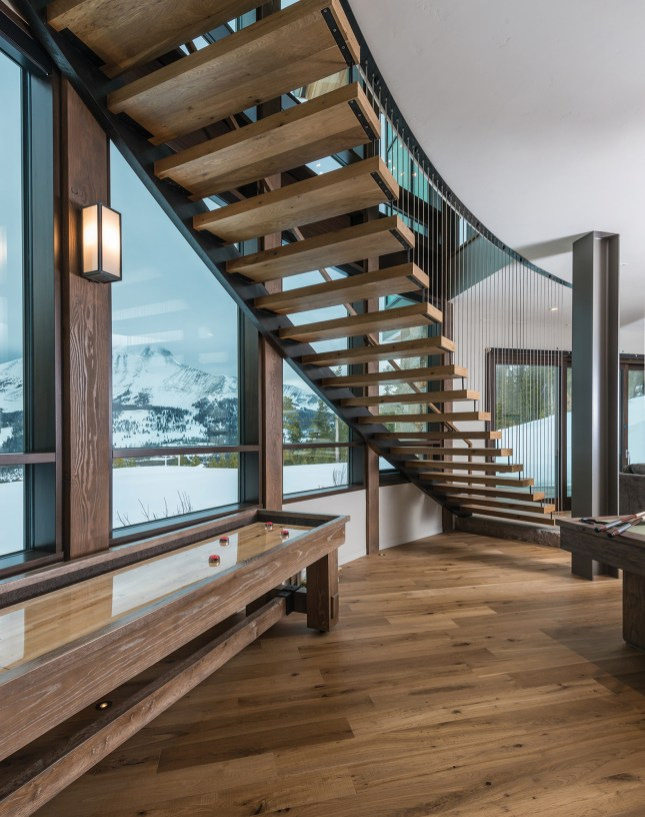 A floating staircase by Brandner Design leads down to the game room area.