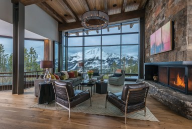 Lone Peak views are highlighted from the great room windows. A tree-stump end table from The Architect's Wife sits next to leather chairs from Montana Expressions. The custom light fixture is by Iron Glass Lighting. A three-paneled painting by the homeowner's father covers the flat-screen TV. SAV Digital Environments automated the panels to open with the touch of a button.