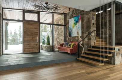 The front entry features a custom light fixture by Iron Glass Lighting and a painting by Pittsburgh, Pennsylvania-based artist Mia Tarducci. The custom staircase, leading to guest quarters, was built by Brandner Design.