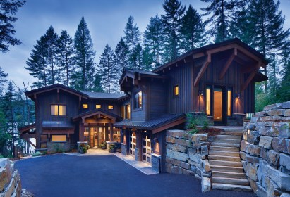 Nestled into the hillside, the home's entry welcomes visitors to the lake beyond.