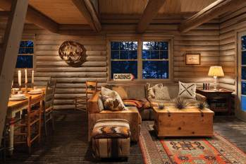 Rustic family heirlooms, including a large, sectional sofa reupholstered with fabric remnants, are used to furnish the cabin.