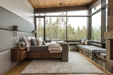 The master bedroom features an upholstered headboard and floating walnut nightstands by Fry Steel and Wood. SAV Digital Environments collaborated with Fry to develop a television lift cabinet, allowing the TV to raise from the bottom of the bed board with a digital control.