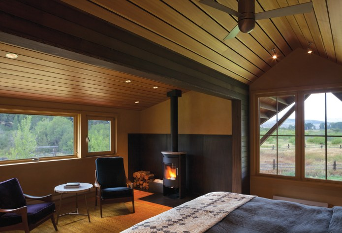 """The master suite, although still modest in size, is the largest bedroom in the home. The family was """"anti-big bedroom,"""" preferring to spend most of their time outdoors. The south facing views off the master bedroom open up to a ridge where elk frequently graze"""