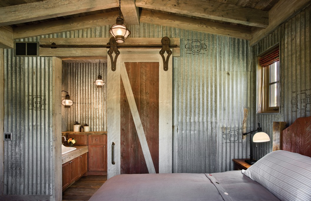 Utilizing galvanized, corrugated metal in a guest bedroom further ties the interior to the agricultural roots of the ranch property.