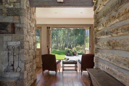 Incorporating stone and reclaimed logs inside the home allows the lines of interior and exterior living to blur beautifully.