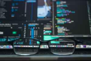 black farmed eyeglasses in front of laptop computer